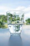 En halva av vatten i exponeringsglaset Royaltyfri Foto