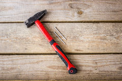 En hammare med ett rött handtag och två spikar Royaltyfria Bilder