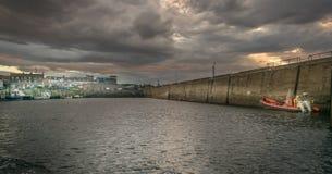 En hamn med fartyg som ses från havet med stormmoln arkivfoto