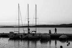 En hamn på en sjö på solnedgången, med olika fartyg och en kvinna t arkivfoto