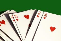 En hand av hjärtor som spelar endast kort på mörkt - grön bakgrund arkivfoton