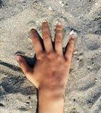 En hand av kvinnan som poseras över sanden av en spansk strand arkivbild