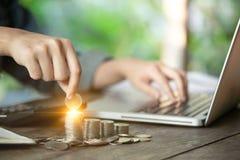 En hand för affärskvinnor rymmer ett mynt för sparande pengarbegrepp och fungerar med hennes datorbärbar dator Ledning till inves royaltyfri foto