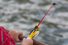 En hand för barn` s fiskar på en liten metspö Ozernaya fiske royaltyfri foto
