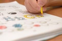 En hand för barn` s skriver och visar engelska bokstäver i en anteckningsbok och alfabet med en blyertspenna och en tuschpenna Arkivbild