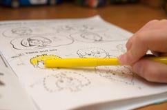 En hand för barn` s skriver och visar engelska bokstäver i en anteckningsbok och alfabet med en blyertspenna och en tuschpenna Fotografering för Bildbyråer