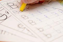 En hand för barn` s skriver och visar engelska bokstäver i en anteckningsbok och alfabet med en blyertspenna och en tuschpenna Arkivfoto
