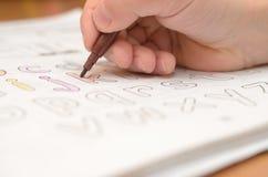 En hand för barn` s skriver och visar engelska bokstäver i en anteckningsbok och alfabet med en blyertspenna och en tuschpenna Royaltyfri Foto
