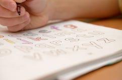 En hand för barn` s skriver och visar engelska bokstäver i en anteckningsbok och alfabet med en blyertspenna och en tuschpenna Royaltyfri Bild