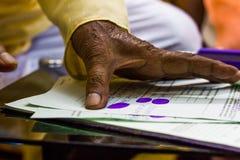 En hand för gamal man` som s ger tummeintrycket på viktiga lagliga dokument Royaltyfria Bilder