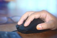 En hand för kvinna` s genom att använda en svart mus Royaltyfri Foto