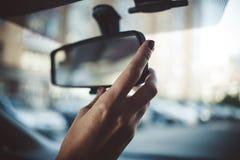 En hand för kvinna` s på rearviewskärmen arkivbild