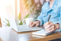En hand för kvinna` som s arbetar på en anteckningsbokdator och skriver på ett n Fotografering för Bildbyråer