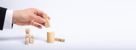 En hand för man` s av en affärsman i en affärsdräkt rymmer ett trädiagram av en man i hans hand och flyttar ett annat diagram royaltyfri foto