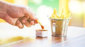 En hand för man` s doppar potatisar in i en apetitousås, pommes frites i en dekorativ hink på en trätabell royaltyfria foton
