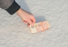 En hand för man` s får några sedlar av den turkiska liraen från snön Arkivfoton