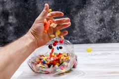 En hand för man` s häller ut blandningen av den kulöra godisen i en plastpåse Royaltyfri Fotografi