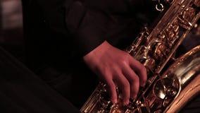 En hand för man` s i en svart dräkt på en guld- saxofon i en jazzband Närbild lager videofilmer