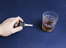 En hand för man` s rymmer biltangenter och alkohol, närbildalkohol royaltyfria foton