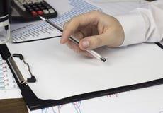 En hand för man` s rymmer en penna på ett tomt ark, en kulvert, en skyddsremsa, affär arkivfoton
