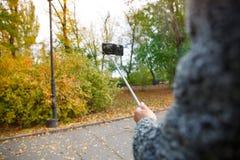 En hand för man` som s rymmer en mobiltelefon med en monopod i ett varmt, parkerar arkivbilder