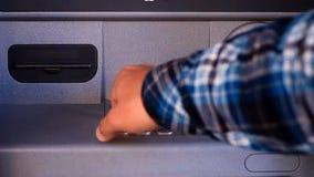 En hand för person` som s sätter in en kreditkort in i en ATM, ett ringande lösenord och ut tar en kreditkort från ATMEN lager videofilmer