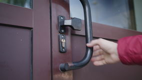 En hand kontrollerar en låst dörr stock video