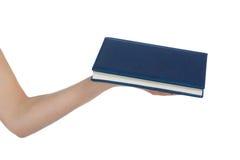 En hand med en blå bok Royaltyfri Foto