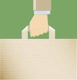 En hand med en pappers- påse Arkivfoto