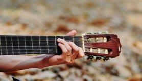 En hand med gitarren Arkivfoton
