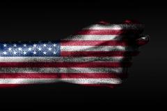 En hand med en m?lad USA flagga visar en barreling, ett tecken av agression, mots?ttning, en tvist p? en m?rk bakgrund royaltyfria foton