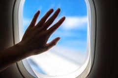 En hand på ett kommersiellt flygplanfönster, kontur arkivbilder
