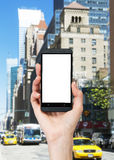 En hand rymmer en smartphone med den vita kopieringsutrymmeskärmen Royaltyfri Fotografi