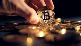 En hand rymmer och vänder en guld- bitcoin av många lager videofilmer