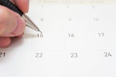 En hand skriver på 15th av kalendern med den mörka grå färgblyertspennan Fotografering för Bildbyråer