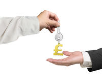 En hand som ger den nyckel- pundsymbolkeyringen till en annan hand, 3D ren Royaltyfri Fotografi