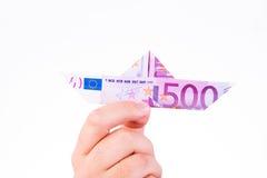 En hand som rymmer ett pappers- fartyg gjort med en anmärkning för euro 500 Royaltyfri Bild