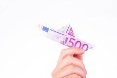 En hand som rymmer ett pappers- fartyg gjort med en anmärkning för euro 500 Royaltyfri Foto