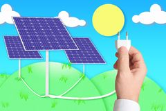 En hand som rymmer en propp, förband till några sol- photovoltaic paneler Royaltyfri Foto