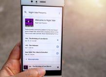 En hand som rymmer en smartphone med 'Welcome till att spela för nattVale' podcast arkivbilder