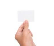 En hand stiger ett tom vitbokkort/anmärkning Arkivbilder