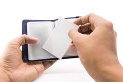 En handaffärsman satte den vita kort- eller namnkontakten in i den blåa läderplånboken på isolerad bakgrund med urklippbanan arkivbilder