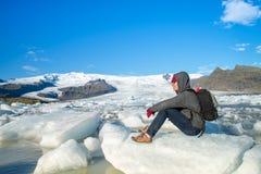 En handelsresande som sitter p? liten is p? den Fjallsarlon glaci?rlagun i sydostliga Island arkivfoto