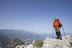 En handelsresande står överst av ett berg och ser ut till havet Royaltyfri Fotografi