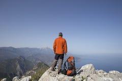 En handelsresande står överst av ett berg och ser ut till havet Royaltyfria Foton