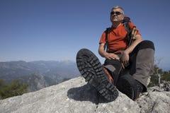 En handelsresande står överst av ett berg och ser ut till havet Fotografering för Bildbyråer