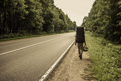 En handelsresandegrabb med en stor ryggsäck går på vägen fotografering för bildbyråer
