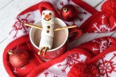 En handgjord marshmallowsnögubbe på en röd kopp med kakao Fotografering för Bildbyråer