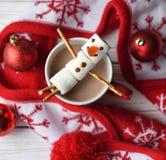 En handgjord marshmallowsnögubbe på en röd kopp med kakao Arkivfoto