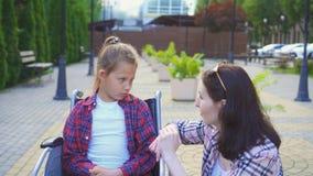En handikappade personertonåring i en rullstol meddelar på gatan med en flicka i en skjorta Arkivbild